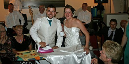 Extreme Ironing at Wedding, ridiculous funny wedding couple photo, wacky wedding, ironing wedding dress, smile couple