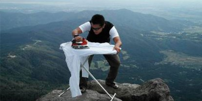 Extreme Ironing on Mountaintop, cool place to do iron clothes, man ironing white clothes, mountain view, windy ironing clothes