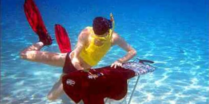 Extreme Ironing Underwater, underwater trip, awesome ironing of clothes, young man tries to iron wet clothes under water